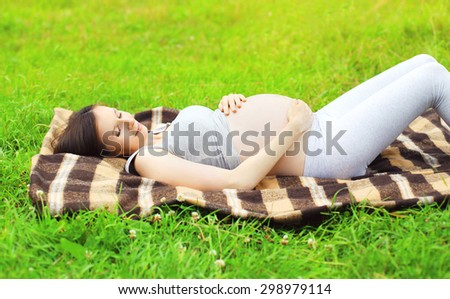Portrait of young pregnant woman resting lying on the grass in summer day - stock photo
