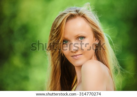 Portrait of young pretty blonde woman at summer green park.