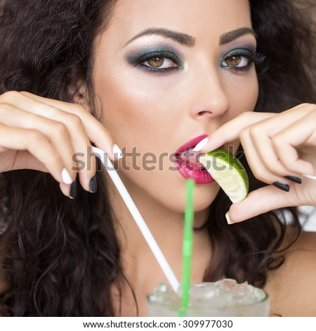 Portrait of young pretty brunette woman with curly hair and bright makeup with alcoholic mojito cocktail from mint soda light rum ice cubes with straw licking lime looking forward, square picture