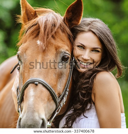 Portrait of young pretty cheerful woman with horse at summer green park.