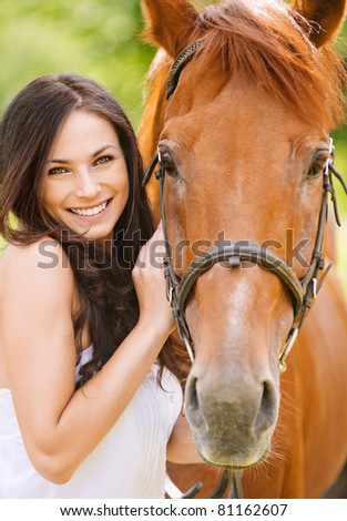 Portrait of young pretty cheerful woman with horse at summer green park. - stock photo