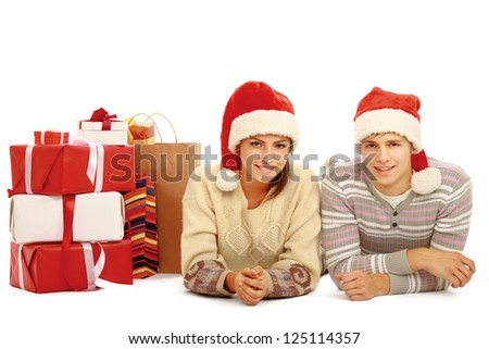 Portrait of young pretty couple lying on the floor near christmas gift and looking at camera. isolated on white background