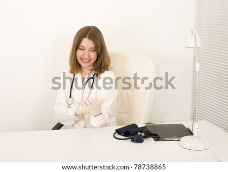 portrait of young pretty doctor with stethoscope smiling sitting at table