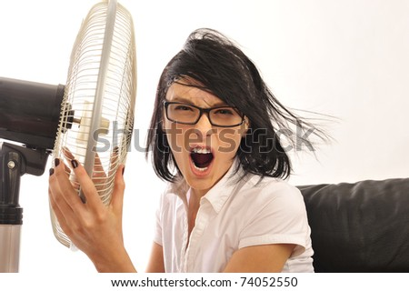Portrait of young pretty expressive woman embracing fan at her workplace.