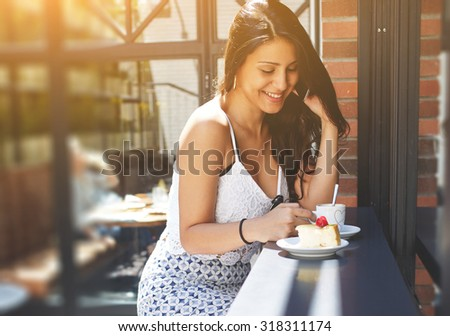 Portrait of young pretty female with excellent figure in elegant summer clothes talking on cell phone while sitting in a coffee shop, gorgeous woman laughing at smart phone conversation, flare sun - stock photo