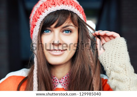 Portrait of young pretty funny smiling girl in cold weather dressed in color clothes and warm hat. Young happy woman having fun outdoor - stock photo