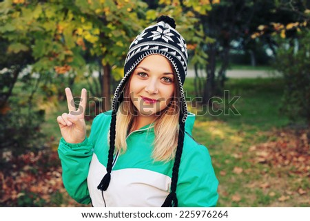 Portrait of young pretty funny smiling girl in cold weather dressed in color sportswear and youth fashion warm hat. Young happy woman having fun outdoor. Photo toned style instagram filters
