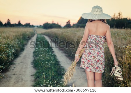 Portrait of young pretty girl at summer weather dressed in bright hat goes on road through a field of wheat - stock photo