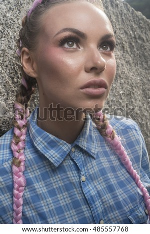 Portrait of young pretty girl with pink plaits wearing blue checked shirt sitting on the rock during summer day