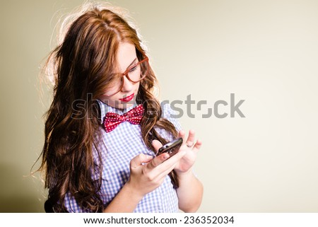 portrait of young pretty lady in bow tie & glasses using mobile phone on light copy space background - stock photo