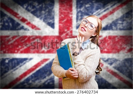 Portrait of young pretty lady in glasses holding books with the UK flag on the background. - stock photo