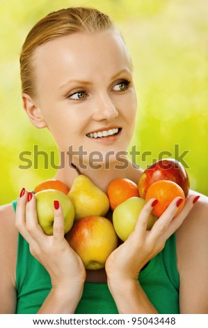 Portrait of young pretty smiling woman holding some fruits at summer green park