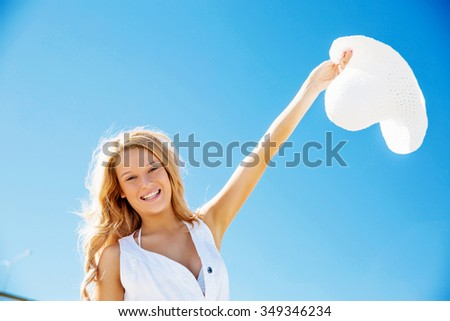 Portrait of young pretty woman cheering and relaxing on sandy beach - stock photo
