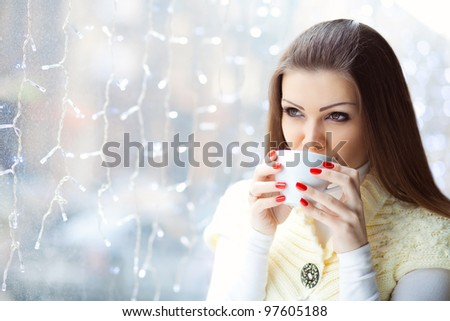 Portrait of young pretty woman drinking coffee in a cafe - stock photo