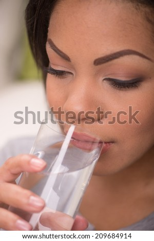 Portrait of young pretty woman drinking. Girl with healthy cool water in glass - stock photo