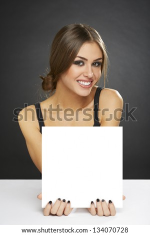 Portrait of young pretty woman holding blank billboard over dark background. - stock photo