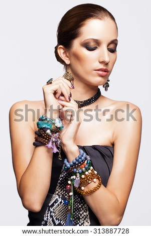 Portrait of young pretty woman in black dress with bijouterie on gray background