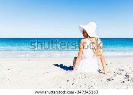 Portrait of young pretty woman in white relaxing on sandy beach