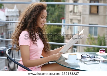 Portrait of young pretty woman reading newspaper at summer terrace in the town