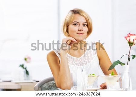 Portrait of young pretty woman sitting at cafe - stock photo
