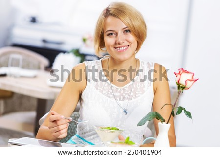 Portrait of young pretty woman sitting at cafe and eating dessert - stock photo
