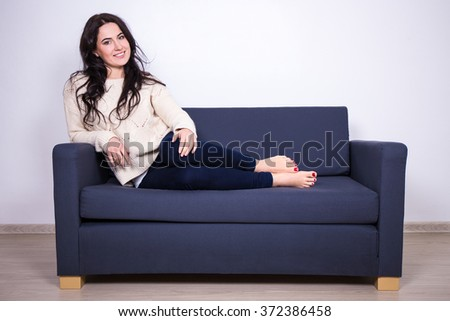 portrait of young pretty woman sitting on sofa at home
