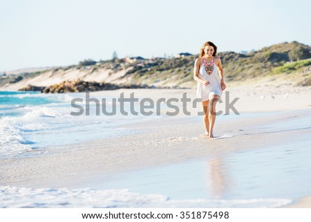 Portrait of young pretty woman walking along sandy beach