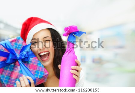 Portrait of young pretty woman wearing Santa Claus helper hat standing inside shopping mall smiling and holding christmas gifts