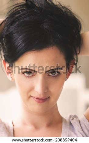Portrait of young pretty woman with a smile on her face, looking to camera - stock photo