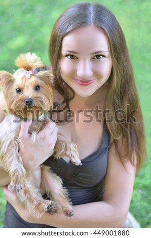 Portrait of young pretty woman with her little yorkshire terrier dog, close up outdoor - stock photo