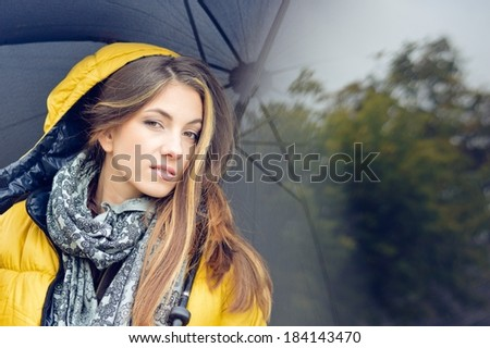 portrait of young pretty woman with umbrella wearing warm yellow coat - stock photo
