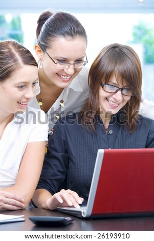 Portrait of young pretty women discussing project in office environment - stock photo