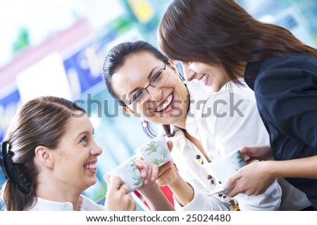 Portrait of young pretty women having coffee break in office environment - stock photo