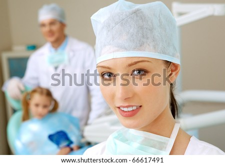 Portrait of young professional looking at camera on background of her colleague and patient - stock photo