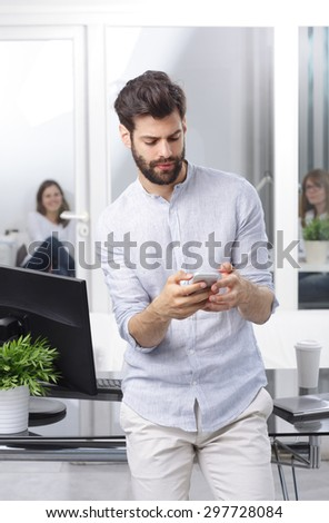 Portrait of young professional man standing at desk in front of computer while holding hand mobile and reading news.