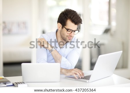 Portrait of young professional sitting at desk and using laptops while working on presentation.