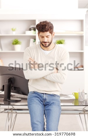 Portrait of young professional standing at office in front of his desk with computer and thinking the solution of the problem. - stock photo