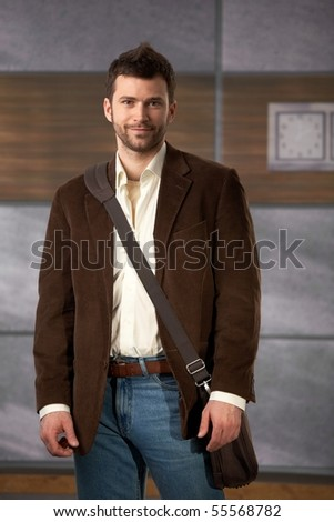 Portrait of young professional standing in office lobby with laptop computer bag on shoulder. - stock photo