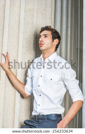 Portrait of Young Professional. Wearing a white shirt, sleeves rolling over, a young college student with a little beard is standing by columns on campus, thinking, confidently looking up.  - stock photo