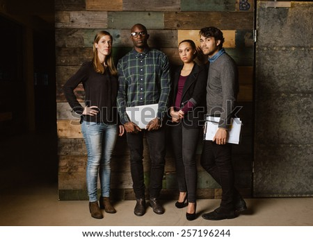 Portrait of young professionals standing together in office. Diverse group of young executives at work. - stock photo