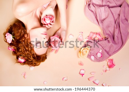 Portrait of young rad haired beautiful woman with stylish bright make-up and roses in her long hair, lying on rose petals background.  - stock photo