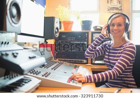Portrait of young radio host wearing headphones using sound mixer in studio - stock photo