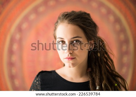 Portrait of young Rastafarian girl looking at the camera - stock photo