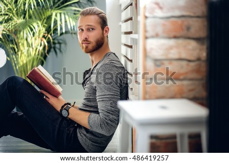 Portrait of young redhead bearded male holding a book in a room with green plants.
