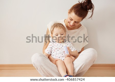 Portrait of young redhead mother having fun with her blond blue-eyed son playing indoor. Caring happy mother enjoying upbringing her lovely baby boy at the weekend at home. Pastel colors, cozy scene  - stock photo