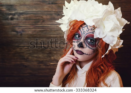 Portrait of young redhead woman with Halloween sugar skull makeup looking at camera. Close up. Wooden backgraund. Copy space, free text. Toned - stock photo