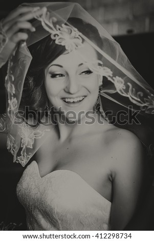 Portrait of young redheaded woman bride, through the wedding veil. Black and white photo - stock photo