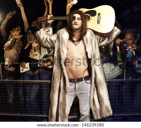 Portrait of young rock musician with guitar posing for excited audience at concert - stock photo
