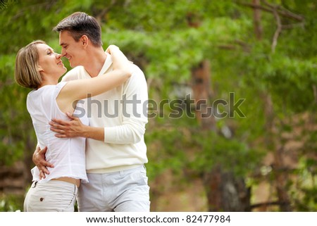 Portrait of young romantic couple embracing in park
