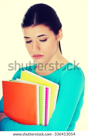 Portrait of young sad female student with workbook. - stock photo